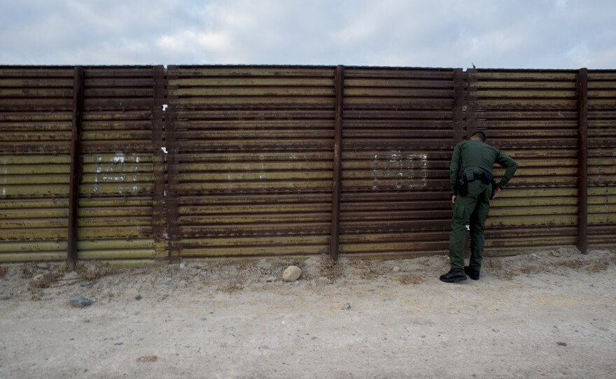 Eduardo Olmos, a Border Patrol public affairs officer, peers through a section of primary fencing between the San Ysidro and Otay Mesa ports of entry in San Diego on Aug. 16, 2017.