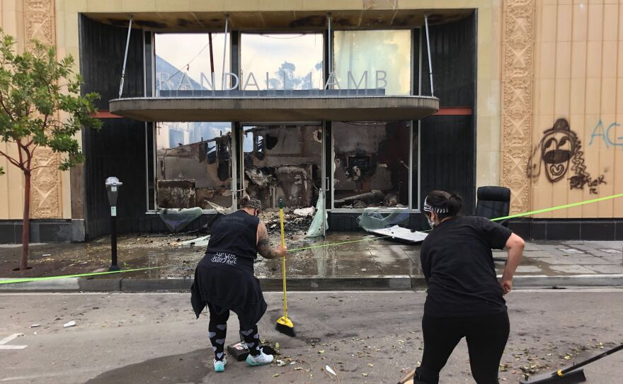 Community members in downtown La Mesa sweep up debris in front of the Randall Lamb Associates building that was burned on the inside, May 31, 2020.