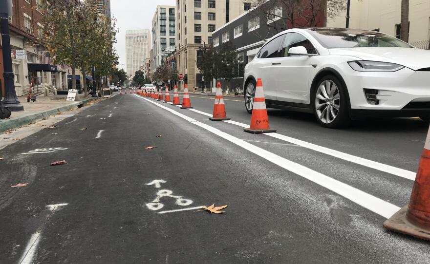 A car drives by orange traffic cones lining a future protected bike lane on J Street near Petco Park, Dec. 21, 2018.