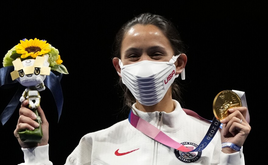 Gold medalist Lee Kiefer of the United States shows her medal and victory bouquet during the medal ceremony for the women's individual Foil final competition on Sunday at the 2020 Summer Olympics.
