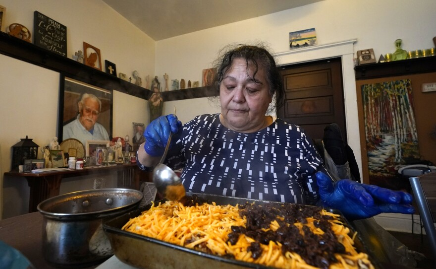 With a portrait of her deceased father on the wall behind, Olga Garcia prepares capirotada, a bread pudding layered with cheese, bananas, raisins, cinnamon and pecans, while preparing an afternoon family meal Wednesday, Nov. 4, 2020, in her home.