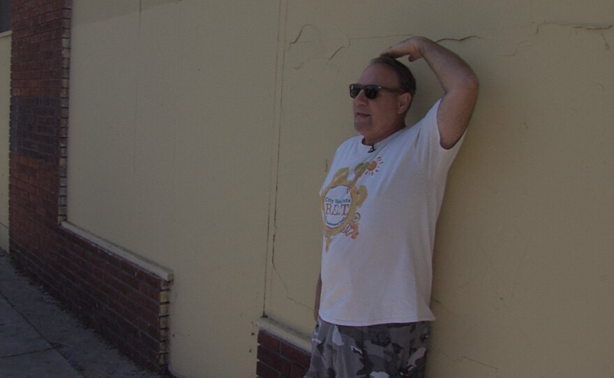 City Heights resident Edwin Lohr leans against the site of a future mural and gestures above his head where he suggested a crown be painted for an interactive art effect, June 9, 2017.