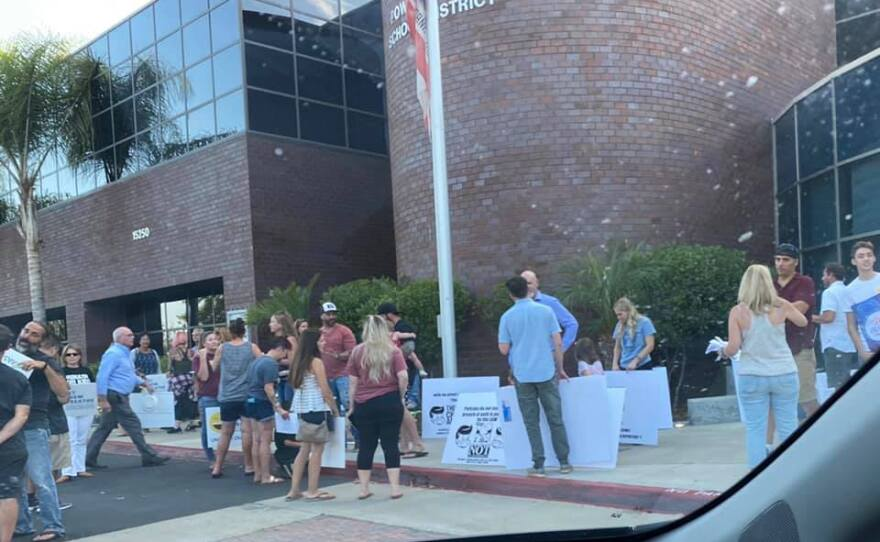 Protestors rally outside the Poway Unified School District offices before a board meeting. September 9, 2021.