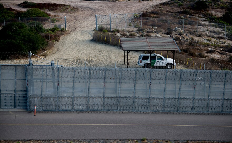A Border Patrol agent vehicle sits between secondary fencing, which includes concertina wire at the top and bottom, and a basic chain-link fence, known as tertiary fencing. Photo was taken on Aug. 16, 2017