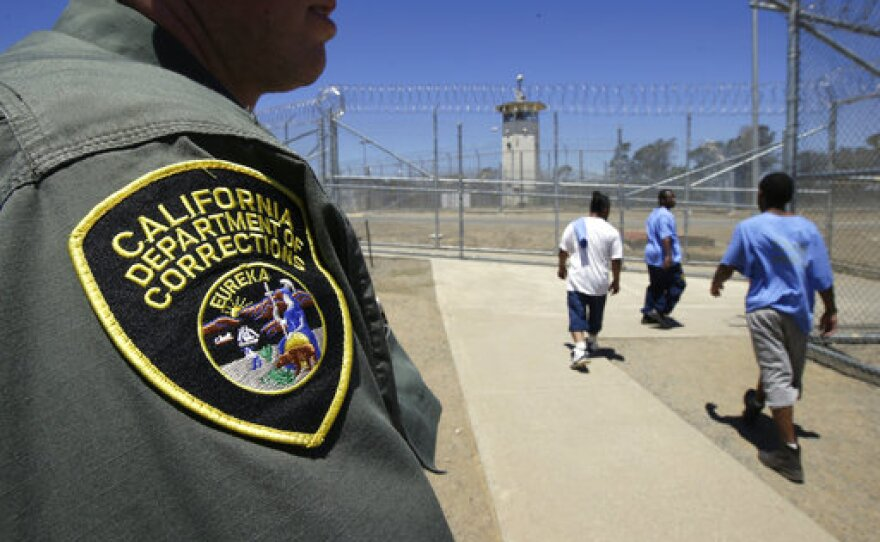 Inmates pass a correctional officer as they leave an exercise yard at the California Medical Facility in Vacaville, Calif., June 20, 2018 .