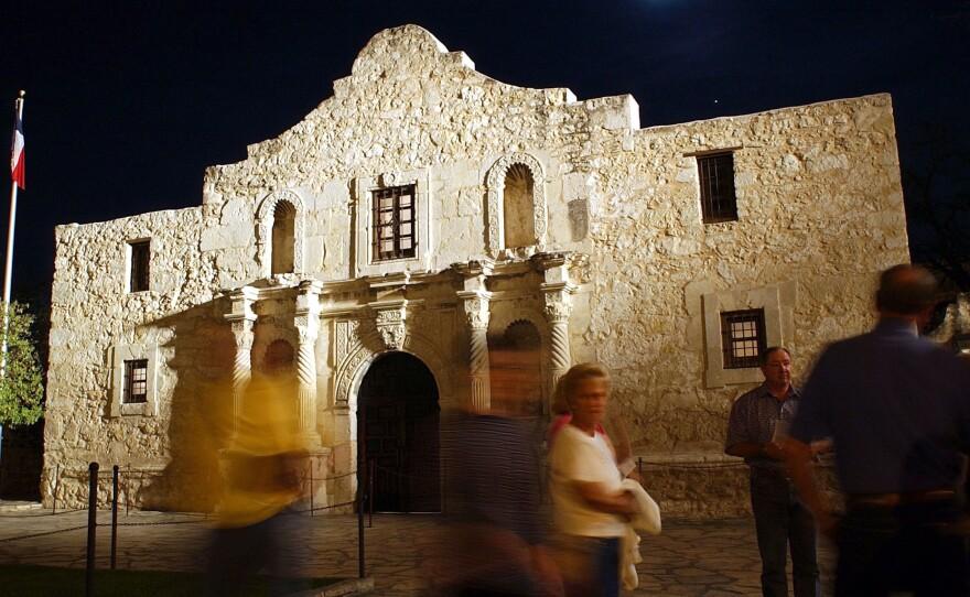 Visitors walk around outside of the Alamo in San Antonio, Texas.
