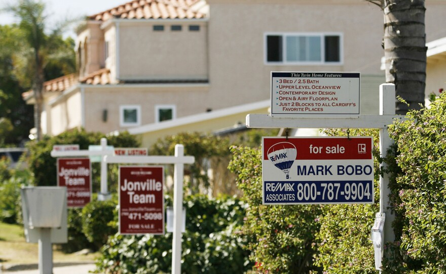 Real estate signs advertise the sale of three houses in a row in Encinitas in San Diego County, July 13, 2006.