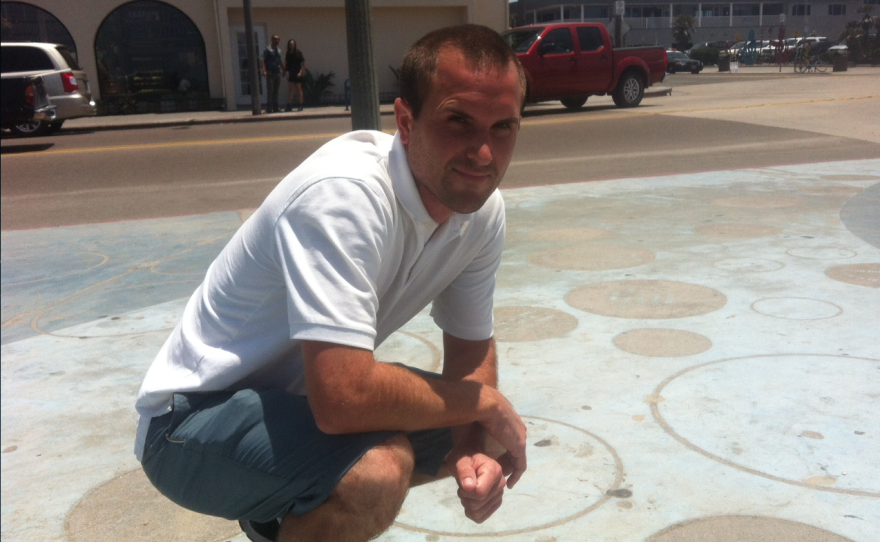 Ocean Beach business owner Steve Grosch squats on the beach community's Veterans Plaza, June 26, 2014.