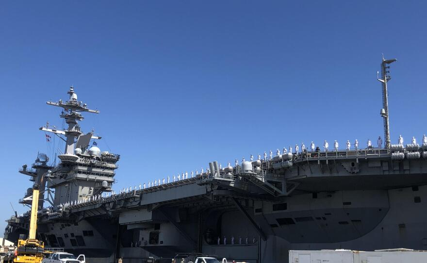 Sailors standing on the deck of the USS Roosevelt as the carrier docks in San Diego for homecoming on July 9, 2020.