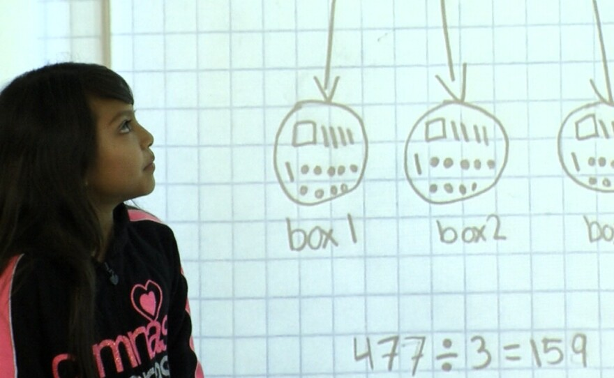 A student in Mymy Chau's fourth-grade class at Perkins Elementary School looks at her classmate's math work on a projector screen.