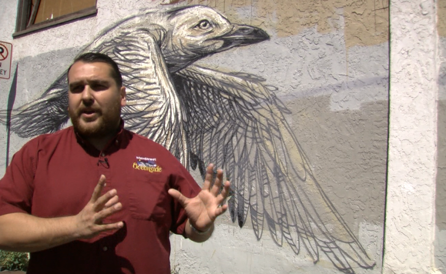 """Gumaro Escarcega of MainStreet Oceanside stands beside an unfinished mural called """"A Flock of Birds,"""" March 28, 2017."""