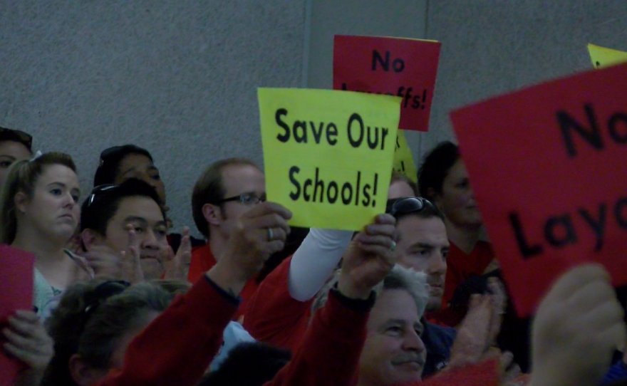 """Parents and educators hold signs reading, """"Save Our Schools,"""" at a San Diego Unified School Board meeting, Feb. 21, 2017."""
