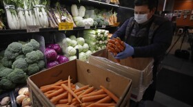 A worker, wearing a protective mask against the coronavirus, stocks produce before the opening of Gus's Community Market, Friday, March 27, 2020, in San Francisco.