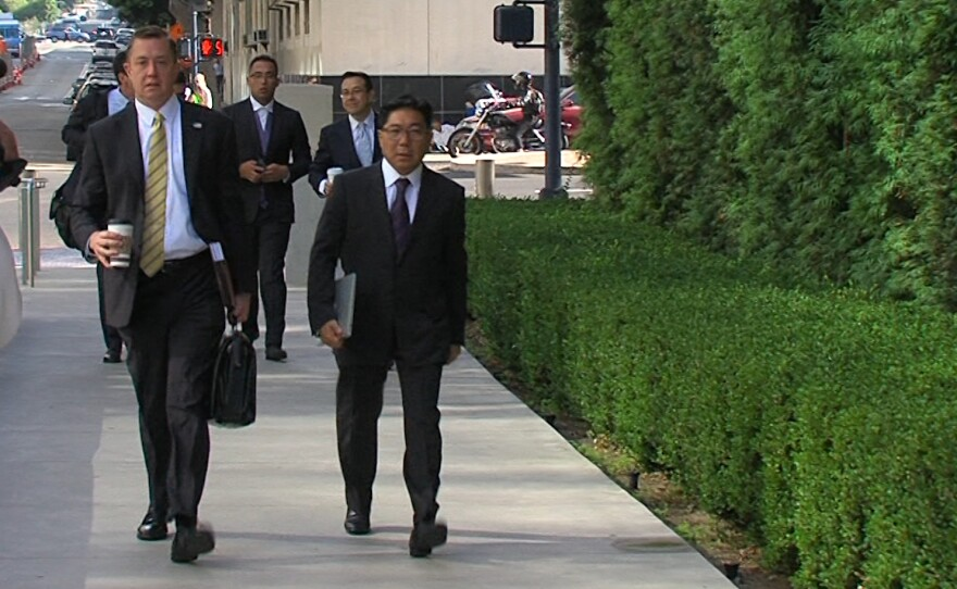 Mexican businessman José Susumo Azano Matsura, right, walks into the federal courthouse in downtown San Diego with his former attorney, Michael Wynne, July 27, 2016.