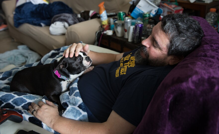 Michael Marquette pets his dog, Spring, while resting at his home in Clarksburg, Md., after a recent hip surgery to repair an injury sustained in 2009 during military duty.
