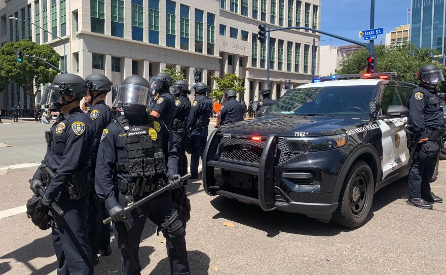 San Diego police officers stand guard on Broadway near State Street in front of City Hall amid protests, May 31, 2020.