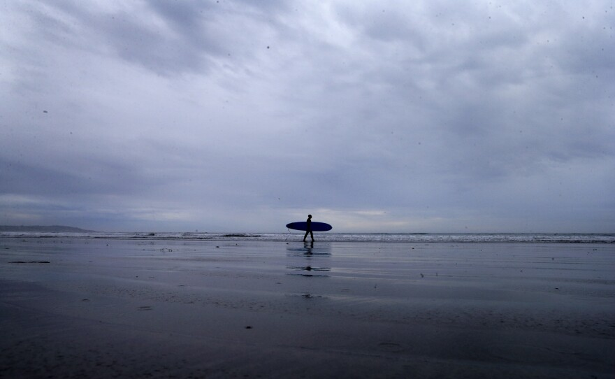 A lone surfer makes his way into the water as storm clouds come ashore in San Diego, Dec. 2, 2014.