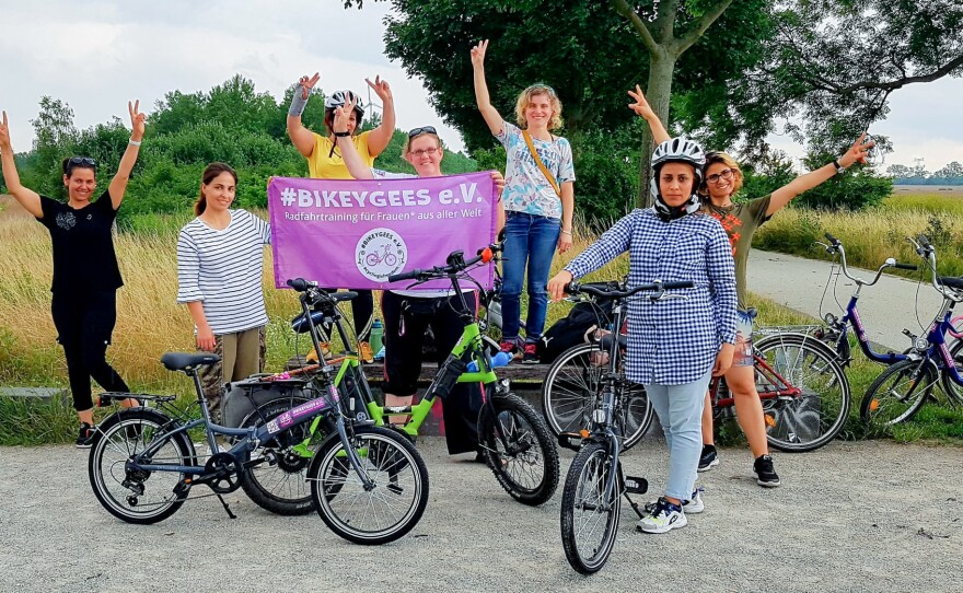 Volunteers and trainees with the group Bikeygees at a park in Berlin in July. The organization teaches refugee women in Germany how to ride bikes. Trainee Shapol Bakir-Rasoul, a refugee from Iraq, holds up a Bikeygees sign with founder Annette Krüger, right. Behind them in yellow is volunteer Shaha Khalef, a refugee from Iraq.