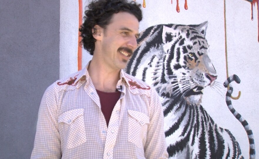 Michael Summers stands next to his tiger mural in Carlsbad, March 28, 2017.