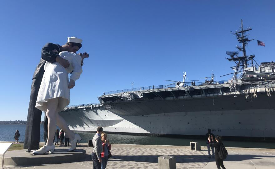 Visitors to the San Diego Embarcadero snap photos next to the 'Embracing Peace' statue near the U.S.S. Midway Museum. The artwork depicts a scene from a famous photo taken in 1945, as an American sailor embraced a woman in New York City's Times Square to celebrate the end of World War 2.