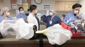 Health care providers gather at the nurses' station in the intensive care unit at Sharp Chula Vista Medical Center, May 1, 2020.