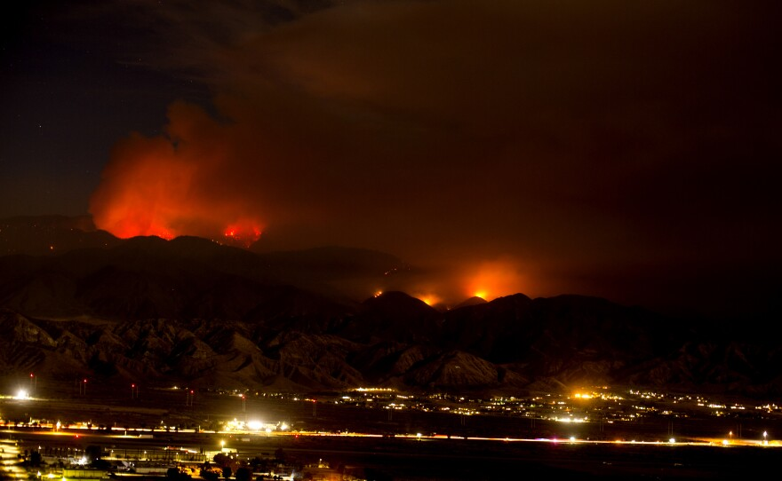 The Apple Fire burns behind mountains near Beaumont, Calif., Sunday, Aug. 2, 2020.