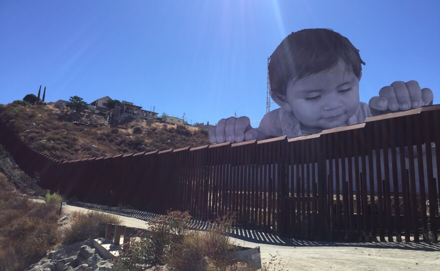 A French photographer constructed a large picture of a baby peeking over the U.S.-Mexico border fence in Tecate, Sept. 11, 2017.