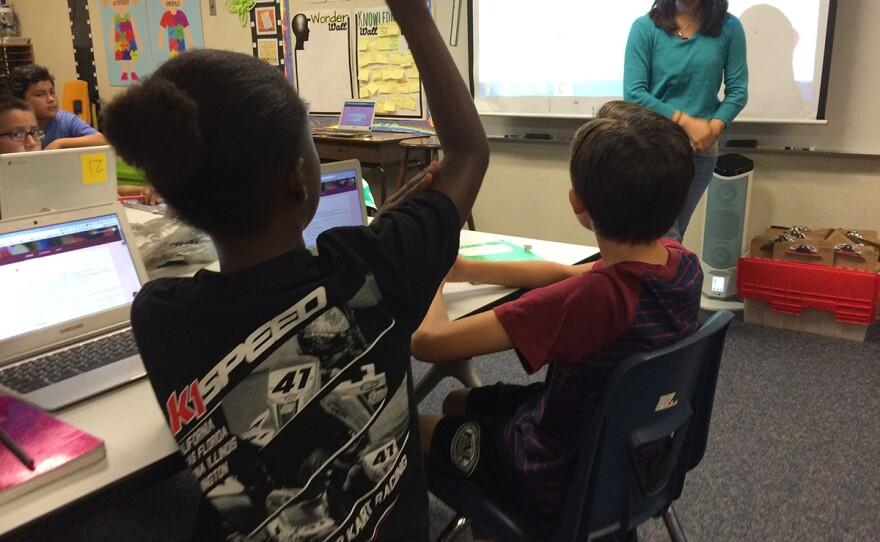 Jada Gill, 10, raises her hand to ask fifth-grade teacher Cindy Lieu a question, Sept. 21, 2016.