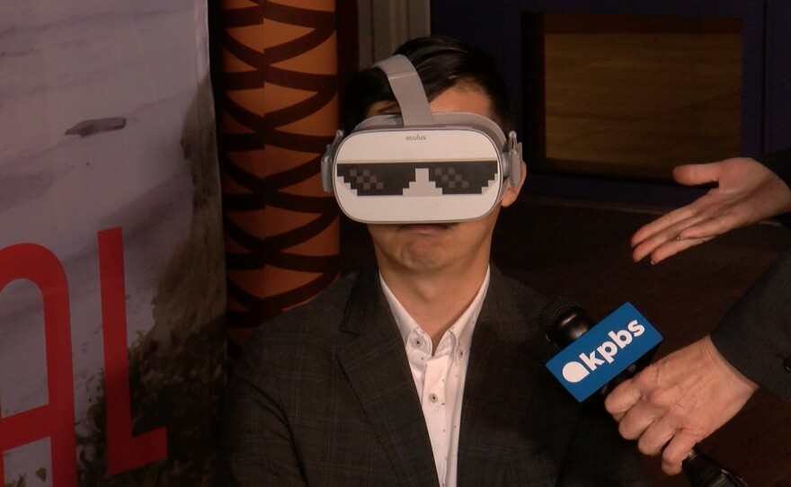 San Diego Asian Film Festival's artistic director Brian Hu demonstrating how to enjoy a VR short playing on opening night of the festival's 20th anniversary. Nov. 7, 2019