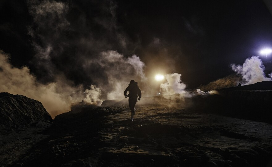 Migrants run as tear gas is thrown by U.S. Border Protection officers to the Mexican side of the border fence after they climbed the fence to get to San Diego, Calif., from Tijuana, Mexico, Tuesday, Jan. 1, 2019.