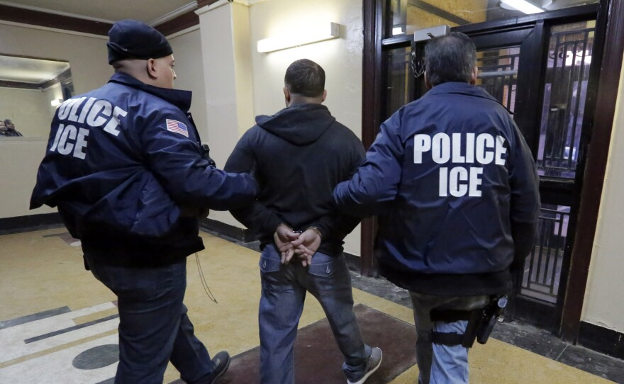 Immigration and Customs Enforcement officers escort a man who was arrested in a New York City apartment building. New York is a city that won't detain noncitizens on behalf of the federal government.