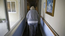 In this Dec. 5, 2019, file photo, a woman walks to her room at a senior care home in Calistoga, Calif.