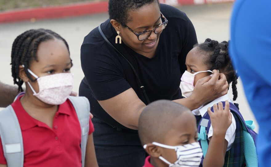 In this Aug. 17, 2021, file photo Leandra Walker, center, helps her daughter Mila Walker, 5, with her mask before she enters school with her siblings Olivia, 7, left, and her twin Max for the first day of classes in Richardson, Texas.