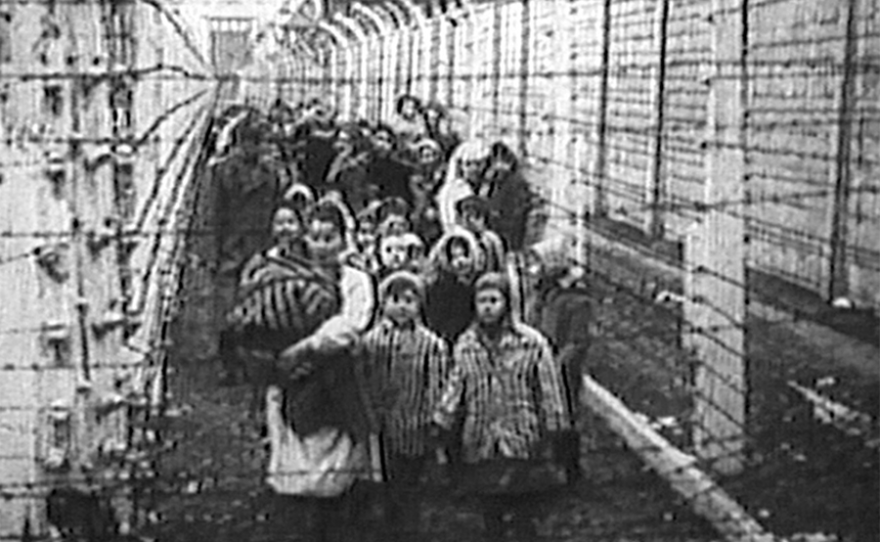 Eva Kor, front middle, and her twin Miriam lead a procession of children between the fences at Auschwitz for the iconic Russian liberation footage. (undated photo)
