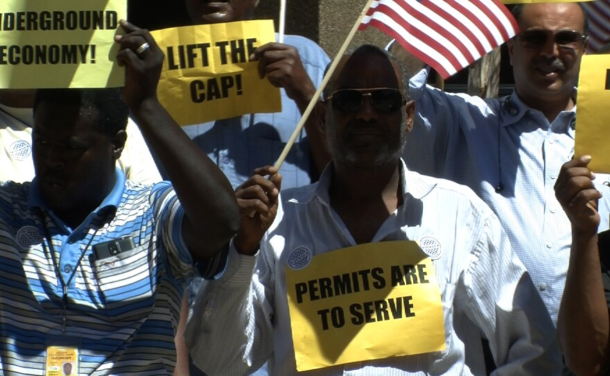 San Diego taxi drivers hold signs and wave American flags at a press conference on Thursday, August 28, 2014 announcing a proposed lift on the number of taxicab permits.
