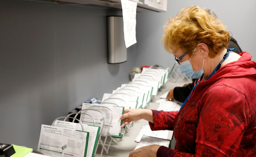 An employee of the West Bloomfield Township Clerks office sorts absentee ballots by the precinct and ballot number at the West Bloomfield Clerks office on October 31, 2020 in West Bloomfield, Mich.