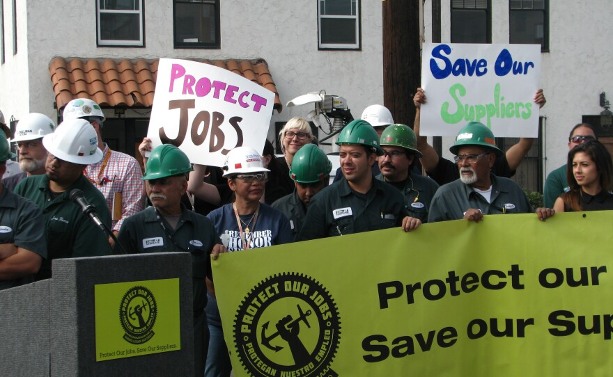 Shipyard workers hold signs as maritime industry kicks off its campaign to overturn the Barrio Logan community plan, Oct 3, 2013.