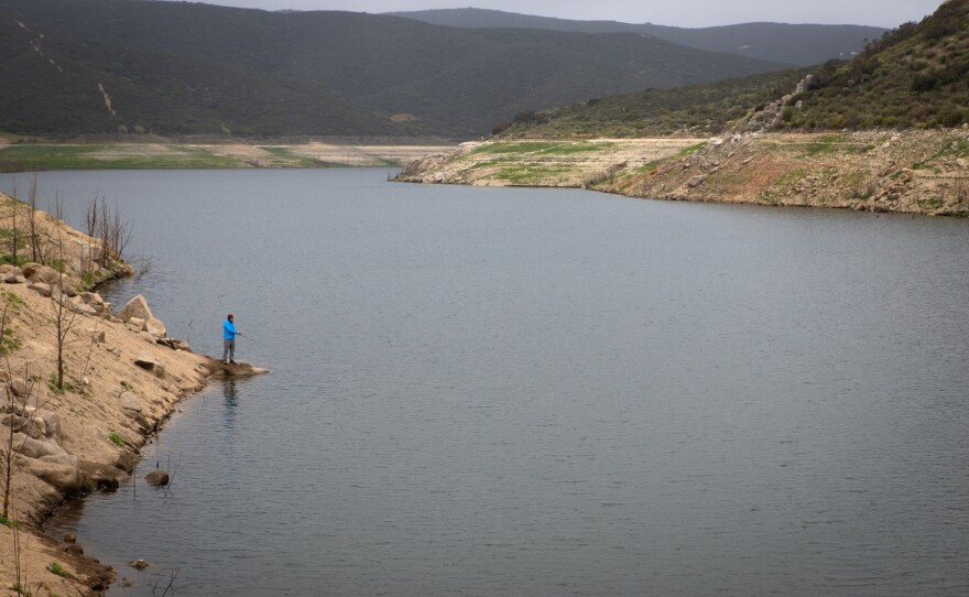 An angler fishes from the shore of Loveland Reservoir, April 13, 2020. A controlled water transfer by Sweetwater Authority has visibly lowered the shoreline level.