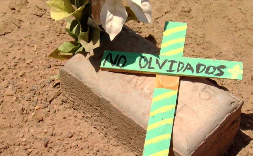 """A memorial cross says, """"We don't forget,"""" in Spanish at Terrace Park Cemetery, June 27, 2016."""