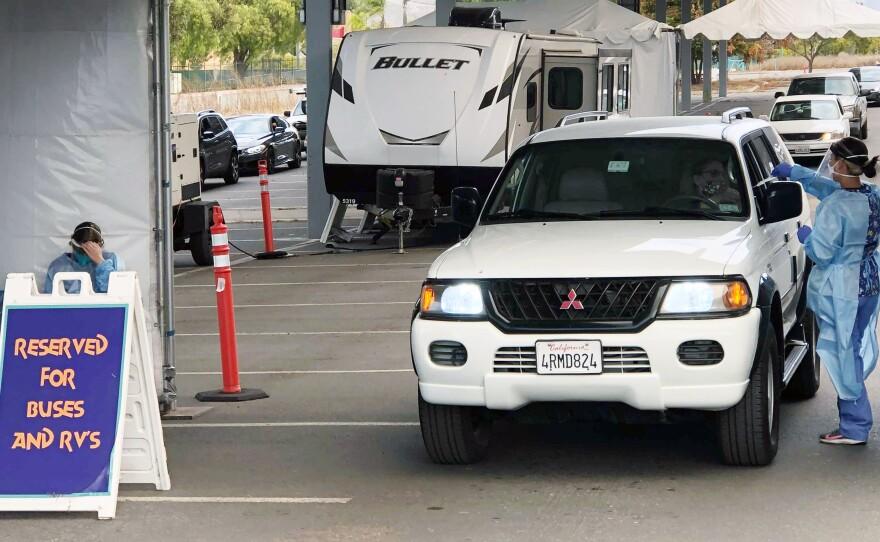 Medical staff administer COVID-19 swab tests at the drive-through Aquatica San Diego testing location, Dec. 8, 2020.
