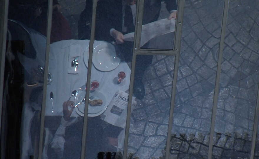 """For the cafe scene, there are panes of glass angled over the cafe so that it reflects what's on the tables and allows the audience a view of the food being served as well a glimpse of the cobblestone texture on the stage floor. All this brings a level of realism to the current San Diego Opera production of """"La Bohème."""""""