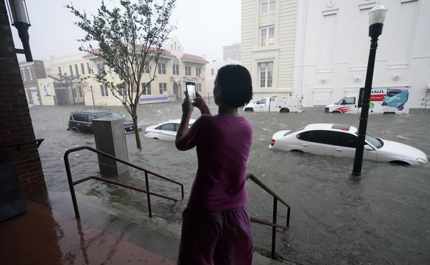 Flood waters swamp cars on a street in downtown Pensacola, Fla., Wednesday. Hurricane Sally made landfall near Gulf Shores, Ala., as a Category 2 storm, pushing a surge of ocean water and dumping torrential rainfall.