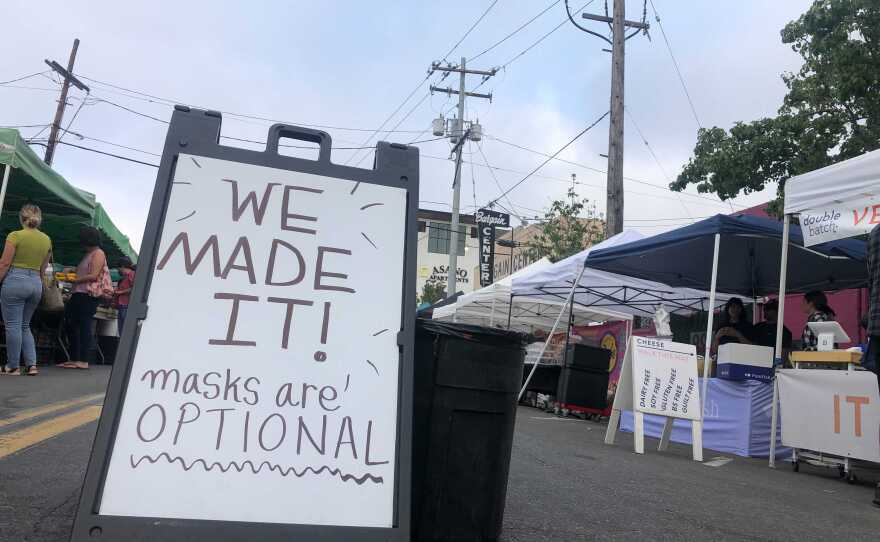 """A sign reads """"We made it! Masks are optional"""" at the North Park Farmers Market in San Diego, Calif. June 17, 2021."""