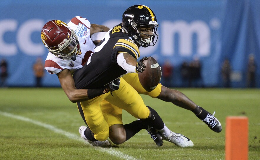Iowa wide receiver Brandon Smith, right, reaches forward as he goes out of bounds as he is tackled by Southern California cornerback Olaijah Griffin during the first half of the Holiday Bowl NCAA college football game Friday, Dec. 27, 2019, in San Diego.