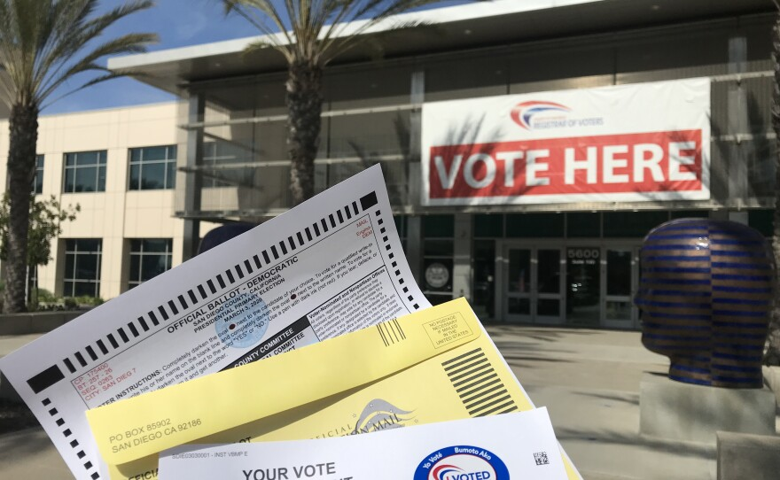 """A mail-in ballot, envelope and the """"I voted"""" sticker are displayed in front of the San Diego County Registrar of Voters office in Kearny Mesa, Feb. 3, 2020."""