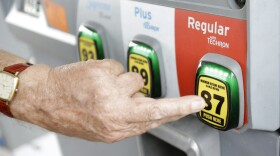 A man selects a grade of gasoline as he fills up his car at a gas station, June 4, 2014.