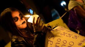 A young girl holds a candle and a sign at a Day of the Dead altar honoring murdered Mexican women and girls on Nov. 3, 2019.
