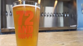 A glass of 72 and Hoppy beer from Bay City Brewing Co. sits atop a counter, July 11, 2017.