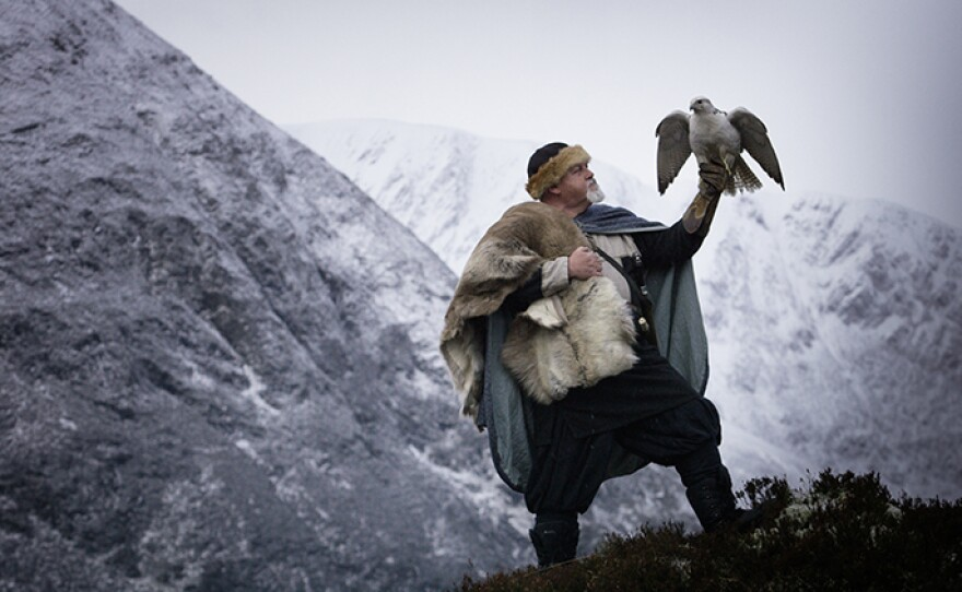 A Viking reenactor and a Gyrfalcon in the snowy landscape of the Alladale Wilderness reserve in Scotland.