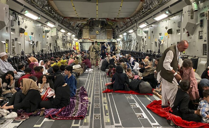 Afghan people sit inside a U.S. military aircraft to leave Afghanistan, at the military airport in Kabul Thursday after Taliban's military takeover of the country.